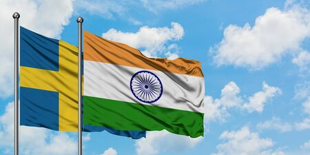 Sweden and India flag waving in the wind against white cloudy blue sky together. Diplomacy concept, international relations.
