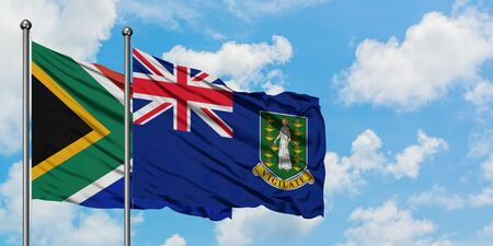 South Africa and British Virgin Islands flag waving in the wind against white cloudy blue sky together. Diplomacy concept, international relations.