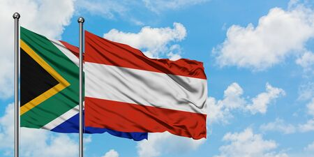South Africa and Austria flag waving in the wind against white cloudy blue sky together. Diplomacy concept, international relations.