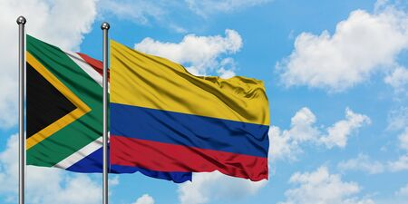 South Africa and Colombia flag waving in the wind against white cloudy blue sky together. Diplomacy concept, international relations.