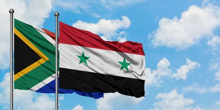 South Africa and Syria flag waving in the wind against white cloudy blue sky together. Diplomacy concept, international relations.
