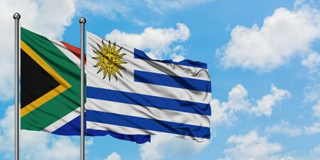 South Africa and Uruguay flag waving in the wind against white cloudy blue sky together. Diplomacy concept, international relations.
