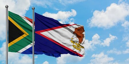 South Africa and American Samoa flag waving in the wind against white cloudy blue sky together. Diplomacy concept, international relations.