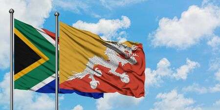South Africa and Bhutan flag waving in the wind against white cloudy blue sky together. Diplomacy concept, international relations.