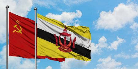 Soviet Union and Brunei flag waving in the wind against white cloudy blue sky together. Diplomacy concept, international relations.