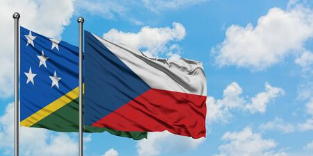Solomon Islands and Czech Republic flag waving in the wind against white cloudy blue sky together. Diplomacy concept, international relations.