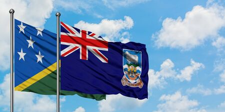 Solomon Islands and Falkland Islands flag waving in the wind against white cloudy blue sky together. Diplomacy concept, international relations.