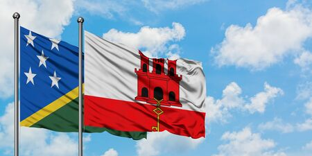 Solomon Islands and Gibraltar flag waving in the wind against white cloudy blue sky together. Diplomacy concept, international relations.