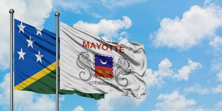 Solomon Islands and Mayotte flag waving in the wind against white cloudy blue sky together. Diplomacy concept, international relations.