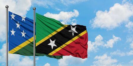 Solomon Islands and Saint Kitts And Nevis flag waving in the wind against white cloudy blue sky together. Diplomacy concept, international relations.