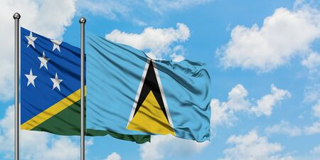 Solomon Islands and Saint Lucia flag waving in the wind against white cloudy blue sky together. Diplomacy concept, international relations.