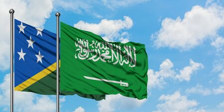 Solomon Islands and Saudi Arabia flag waving in the wind against white cloudy blue sky together. Diplomacy concept, international relations.