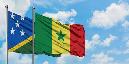 Solomon Islands and Senegal flag waving in the wind against white cloudy blue sky together. Diplomacy concept, international relations.