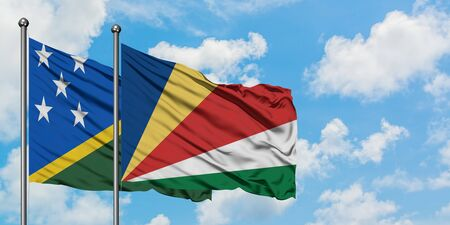 Solomon Islands and Seychelles flag waving in the wind against white cloudy blue sky together. Diplomacy concept, international relations.