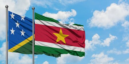 Solomon Islands and Suriname flag waving in the wind against white cloudy blue sky together. Diplomacy concept, international relations.