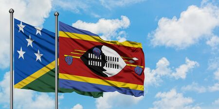 Solomon Islands and Swaziland flag waving in the wind against white cloudy blue sky together. Diplomacy concept, international relations.