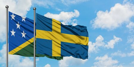 Solomon Islands and Sweden flag waving in the wind against white cloudy blue sky together. Diplomacy concept, international relations.