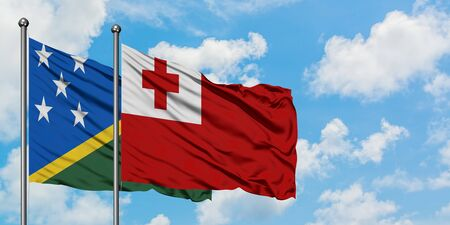Solomon Islands and Tonga flag waving in the wind against white cloudy blue sky together. Diplomacy concept, international relations.