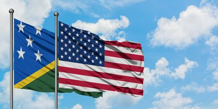 Solomon Islands and United States flag waving in the wind against white cloudy blue sky together. Diplomacy concept, international relations.