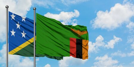 Solomon Islands and Zambia flag waving in the wind against white cloudy blue sky together. Diplomacy concept, international relations. Stok Fotoğraf