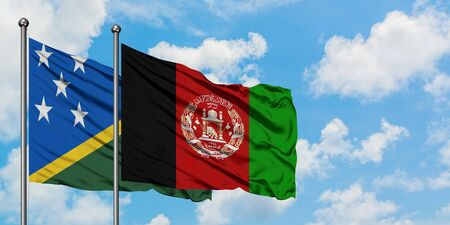 Solomon Islands and Afghanistan flag waving in the wind against white cloudy blue sky together. Diplomacy concept, international relations.