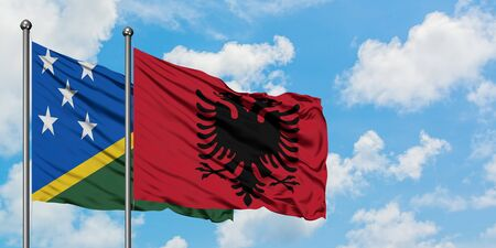 Solomon Islands and Albania flag waving in the wind against white cloudy blue sky together. Diplomacy concept, international relations.
