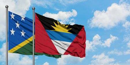 Solomon Islands and Antigua and Barbuda flag waving in the wind against white cloudy blue sky together. Diplomacy concept, international relations.