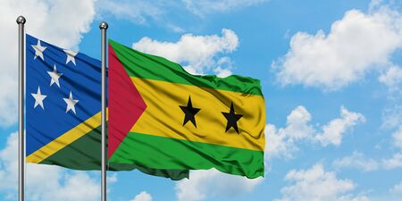 Solomon Islands and Sao Tome And Principe flag waving in the wind against white cloudy blue sky together. Diplomacy concept, international relations.