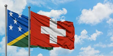Solomon Islands and Switzerland flag waving in the wind against white cloudy blue sky together. Diplomacy concept, international relations.