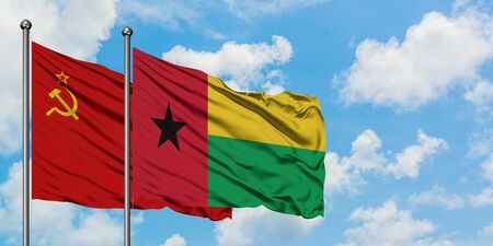 Soviet Union and Guinea Bissau flag waving in the wind against white cloudy blue sky together. Diplomacy concept, international relations.