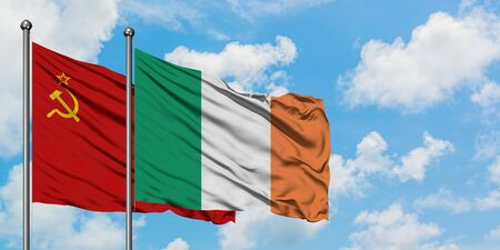 Soviet Union and Ireland flag waving in the wind against white cloudy blue sky together. Diplomacy concept, international relations.