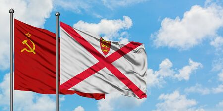 Soviet Union and Jersey flag waving in the wind against white cloudy blue sky together. Diplomacy concept, international relations.