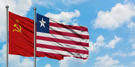 Soviet Union and Liberia flag waving in the wind against white cloudy blue sky together. Diplomacy concept, international relations.