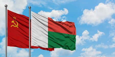 Soviet Union and Madagascar flag waving in the wind against white cloudy blue sky together. Diplomacy concept, international relations.