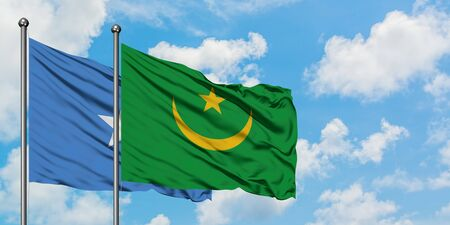 Somalia and Mauritania flag waving in the wind against white cloudy blue sky together. Diplomacy concept, international relations. Фото со стока