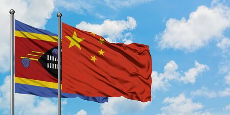 Swaziland and China flag waving in the wind against white cloudy blue sky together. Diplomacy concept, international relations. 版權商用圖片