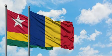 Togo and Romania flag waving in the wind against white cloudy blue sky together. Diplomacy concept, international relations.