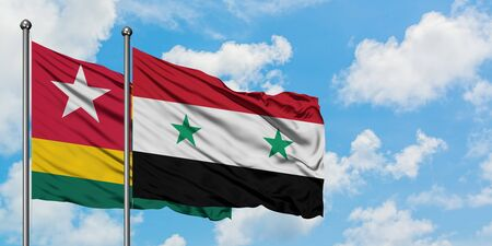 Togo and Syria flag waving in the wind against white cloudy blue sky together. Diplomacy concept, international relations. Banco de Imagens