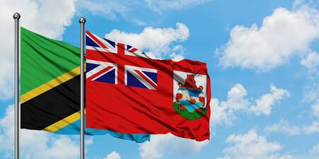 Tanzania and Bermuda flag waving in the wind against white cloudy blue sky together. Diplomacy concept, international relations.