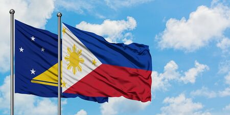 Tokelau and Philippines flag waving in the wind against white cloudy blue sky together. Diplomacy concept, international relations.