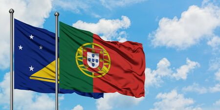 Tokelau and Portugal flag waving in the wind against white cloudy blue sky together. Diplomacy concept, international relations.