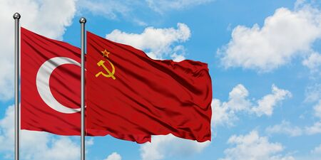 Turkey and Soviet Union flag waving in the wind against white cloudy blue sky together. Diplomacy concept, international relations.