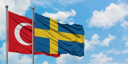 Turkey and Sweden flag waving in the wind against white cloudy blue sky together. Diplomacy concept, international relations.