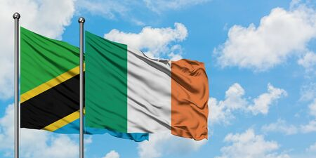 Tanzania and Ireland flag waving in the wind against white cloudy blue sky together. Diplomacy concept, international relations. Banque d'images