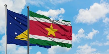 Tokelau and Suriname flag waving in the wind against white cloudy blue sky together. Diplomacy concept, international relations.