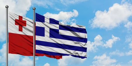 Tonga and Greece flag waving in the wind against white cloudy blue sky together. Diplomacy concept, international relations. Standard-Bild