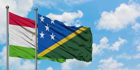 Tajikistan and Solomon Islands flag waving in the wind against white cloudy blue sky together. Diplomacy concept, international relations. Stok Fotoğraf