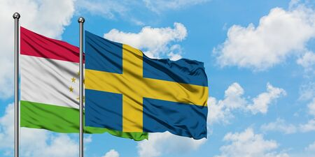 Tajikistan and Sweden flag waving in the wind against white cloudy blue sky together. Diplomacy concept, international relations. Standard-Bild