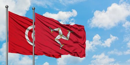 Tunisia and Isle Of Man flag waving in the wind against white cloudy blue sky together. Diplomacy concept, international relations. Banque d'images