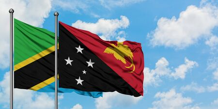 Tanzania and Papua New Guinea flag waving in the wind against white cloudy blue sky together. Diplomacy concept, international relations.